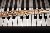14 K rose gold flute on a piano — Stock Photo