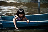 A girl uses her hand sailing a boat in the flood — Stock Photo