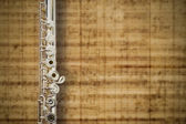 Middle joint of the flute on an abstract music score background — Stock Photo