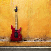 Red Old Guitar on a Grudge Yellow Wall — Stock Photo