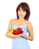 Isolated young asian woman with a red and yellow paprika — Stock Photo