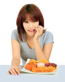 Isolated young asian woman with a donuts on the table — Stock Photo