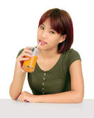 Young asian woman with a glass of orange juice — Stock Photo