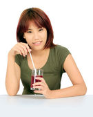 Isolated young asian woman with a cglass of grape juice — Stock Photo