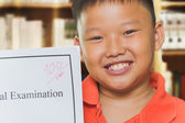 Young asian boy with full score examination sheets — Stock Photo