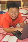 Asian boy working on a laptop computer — Foto Stock