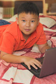 Asian boy working on a laptop computer — Stockfoto