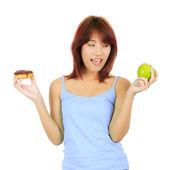Giovane donna asiatica con una mela e un pezzo di ciambella — Foto Stock