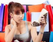 Isolated young Asian woman with shopping bags and new shoes — Stock Photo