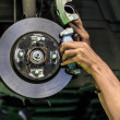 图库照片: Hands of mechanic install brake lining onto car disc brake