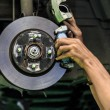 Hands of mechanic install brake lining onto car disc brake — Photo #32481221
