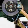 Hands of mechanic install brake lining onto car disc brake — ストック写真 #32481259