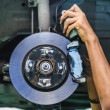 Foto Stock: Hands of mechanic install brake lining onto car disc brake