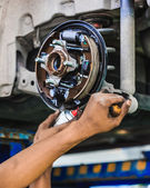 Hands of a mechanic adjusting a car drum brake — Stock Photo