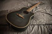 Old dusty acoustic cutaway guitar in bed in a daken bedroom — Foto Stock