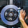 Постер, плакат: Hands of a mechanic install brake lining onto a car disc brake