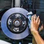 Hands of a mechanic install brake lining onto a car disc brake — Stock Photo