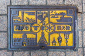 Signs and symbols of important places on a Manhole in Kobe — Stock Photo
