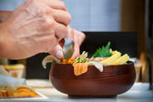 Closeup of a bowl of Sashimi with hands of Japanese chef — Stockfoto