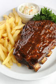 Grilled barbecue ribs and fries — Stock Photo