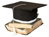 Mortar board on a stack of books — Stock Photo