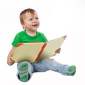 Smiling little boy with a book sitting on the floor — Stock Photo
