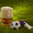 Stock Photo: Mug of fresh lager beer, vuvuzeland small soccer ball on g
