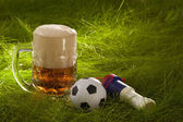 Mug of fresh lager beer, vuvuzela and small soccer ball on the g — Stock Photo