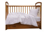 Wooden cot with bedding — Stock Photo