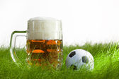 Mug of beer and soccer ball on grass — Stock Photo