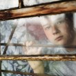The boy looks out of the window through a lattice — Foto Stock