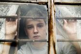 The boy looks out of the window through a lattice — Stock Photo