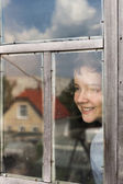 The boy cheerfully looks out of the window — Stock Photo