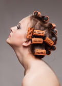Stylish girl portrait with fashion makeup and hair curlers, isol — Stock Photo