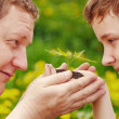 Man and boy holding green plant in hands. — Stock Photo