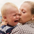 Portrait of a crying little boy who is being held by her mother — Stock Photo