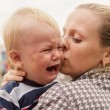 Stock Photo: Portrait of crying little boy who is being held by her mother