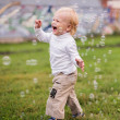 Little  boy  runs and  catches soap bubbles — Stock Photo