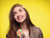 Happy young girl with lollipop on a yellow — Stockfoto