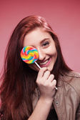 Happy young girl with lollipop on a pink — Stockfoto