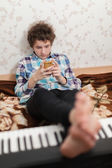 Game in a mobile phone is more interesting, than on the piano — Stockfoto