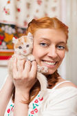 Red-haired girl with a red kitten — Stock Photo