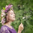 Cute girl in a wreath of lilacs blowing on a dandelion  — Stock Photo #48415937