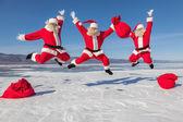 Three Jumping Santa Claus outdoors — Stock Photo