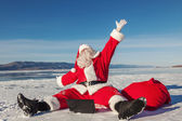 Santa Claus sitting on snow glad news in the laptop — Stock Photo