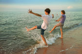 Boy and girl having fun sprinkled sea waves — Stock Photo