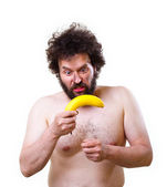 Wild man looking confused at a banana — Stock Photo