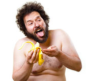Caveman eating a banana — Stock Photo