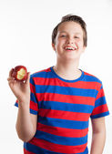 Teenager holding apple into camera — Stock Photo