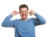 Caucasian casual man, protecting ears from loud noises — Stock Photo